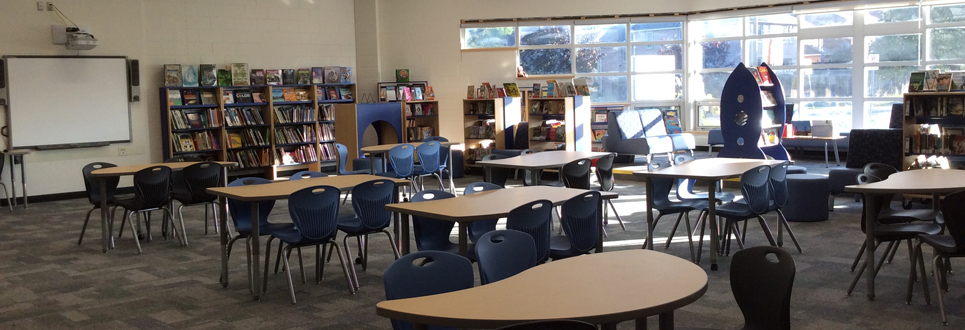 Learning Commons with blue bench seating, book shelves and tables.