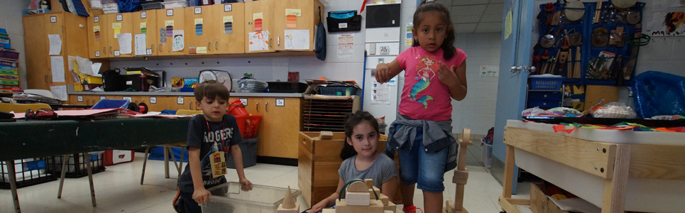 Three younger students, a boy and two girls playing with wooden blocks.